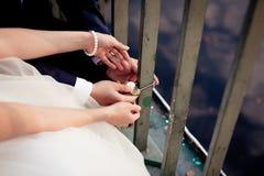 Les nouveaux mariés fixent la serrure sur le pont Images stock