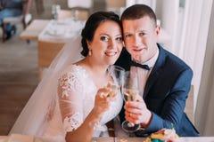 Les nouveaux mariés heureux boivent le champagne et l'embrassement célébrant leur nouvelle vie mariée Photo libre de droits