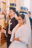 Les nouveaux mariés heureux tiennent les bougies avec les rubans blancs tout en se tenant sous les couronnes d'or Image stock