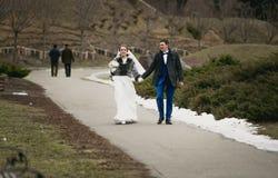 Les nouveaux mariés marchant sur la route à l'hiver se garent photos libres de droits
