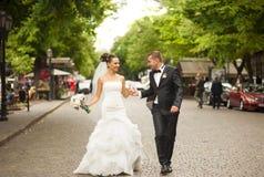 Les nouveaux mariés marchent sur la rue Image stock