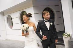 Les nouveaux mariés marchent sur le fond de bâtiment Images libres de droits