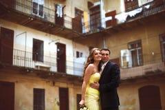 Les nouveaux mariés posent dans l'avant de la vieille maison avec des balcons Images libres de droits