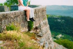 Les nouveaux mariés s'asseyent sur le précipice Jambes en gros plan Weddi Image stock