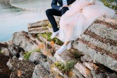 Les nouveaux mariés s'asseyent sur le précipice Jambes en gros plan Weddi Image libre de droits
