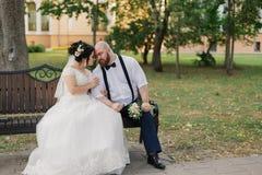 Les nouveaux mariés s'asseyent sur un banc en parc photos stock