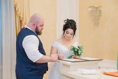 Les nouveaux mariés signent un contrat de mariage au bureau d'enregistrement images libres de droits