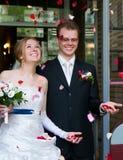 Les nouveaux mariés sous les pétales roses Photographie stock libre de droits