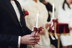 Les nouveaux mariés tiennent des bougies tout en priant dans l'église Image stock