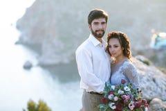 Les nouveaux mari?s ?l?gants caressent en nature, sur le fond des roches et des falaises photographie stock