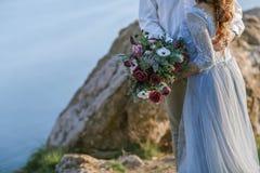 Les nouveaux mari?s ?l?gants caressent en nature, sur le fond des roches et des falaises image stock
