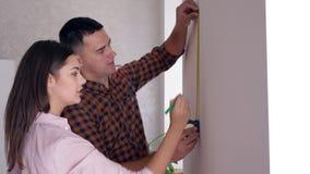 Les nouveaux propriétaires heureux avec le ruban métrique faisant la rénovation dans la chambre et communiquent banque de vidéos
