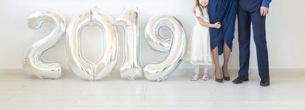 Les nouvel 2019 ans sont le prochain concept - fin vers le haut de la position de famille près des nombres colorés argentés à l'i photographie stock