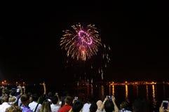 Les nouvelles années d'éclat de feux d'artifice dans le ciel comme personnes observent et enregistrent Photographie stock libre de droits