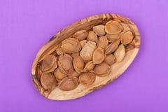 Les noyaux d'abricot sec la graine d'un abricot, ont souvent appel? une ?pierre ?dans la cuvette en bois sur le pourpre Amygdalin image libre de droits