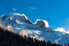 Les nuages de tempête soufflant au-dessus de la neige ont couvert les crêtes alpines en hiver photographie stock libre de droits