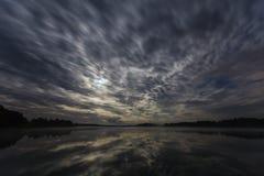 Les nuages dynamiques pendant la nuit au-dessus du lac se sont allumés par la pleine lune image libre de droits