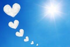 les nuages en forme de coeur sur le ciel bleu et le soleil brille Image stock