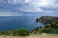 Les nuages et la pluie au-dessus de la mer Photographie stock libre de droits