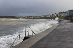Les nuages et les vagues de rupture foncés à la plage de Ballyholme promenade à Bangor Irlande du Nord pendant une tempête d'hive Images libres de droits