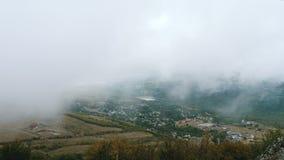 Les nuages flottent au-dessus du village de montagne banque de vidéos