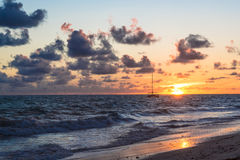 Les nuages foncés pelucheux flottant au-dessus des eaux turbulentes d'océan sur la plage sablonneuse étayent Image stock
