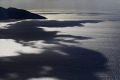 Les nuages ont réfléchi sur la mer Photo stock
