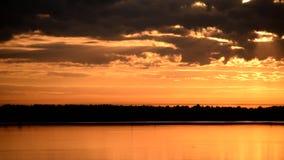 Les nuages oranges et jaunes éclairés à contre-jour dramatiques se déplacent au-dessus de l'eau clips vidéos