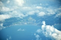 Les nuages regardent et ville du Japon de la fenêtre de l'avion Image libre de droits