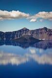 Les nuages se reflètent dans l'eau bleue claire au lac crater Image libre de droits