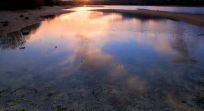 Les nuages se sont reflétés dans l'eau d'un lac Image stock
