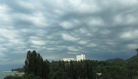 Les nuages sous une forme de vagues sont au-dessus des montagnes Photo stock