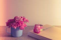 Les oeillets roses lumineux fleurissent dans la tasse bleue, sur le livre de papier classique Photographie stock