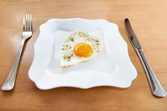 Les oeufs au plat à un coeur forment d'un plat et des couverts blancs Photo libre de droits