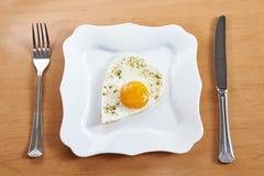 Les oeufs au plat à un coeur forment d'un plat et des couverts blancs Image stock