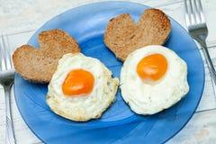 Les oeufs au plat avec du pain grillé sous forme de coeur pour l'amour déjeunent Photographie stock libre de droits