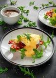 Les oeufs Benoît sur le petit pain anglais avec le lard croustillant, la salade de fusée sauvage et le hollandaise sauce Images libres de droits
