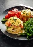 Les oeufs Benoît sur le petit pain anglais avec les saumons fumés, la fusée sauvage et le hollandaise sauce dans un plat noir Image libre de droits