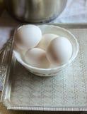 Les oeufs blancs se situent dans une cuvette avec un certain nombre de casserole debout Photographie stock