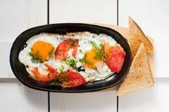 Les oeufs brouillés avec les tomates fraîches et les herbes fraîches ont fait frire dans une casserole Servi avec du pain grillé  Image stock