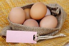 Les oeufs bruns de poulet dans le sac mettent en sac avec l'étiquette de papier blanc Photographie stock
