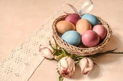 Les oeufs colorés avec les bourgeons et le satin roses cintrent dans un panier wattled Photo stock
