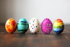 Les oeufs colorés de Pâques sur le fond en bois avec l'oeuf ont formé des mots Joyeuses Pâques Photographie stock libre de droits