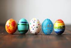 Les oeufs colorés de Pâques sur le fond en bois avec l'oeuf ont formé des mots Joyeuses Pâques Photographie stock