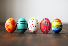 Les oeufs colorés de Pâques sur le fond en bois avec l'oeuf ont formé des mots Joyeuses Pâques Photo stock