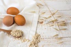 Les oeufs de Brown, farine d'avoine sèche s'écaille sur la cuillère en bois dispersée au-dessus du tissu de toile blanc, fond en  Photos libres de droits