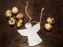 Les oeufs de caille sont sur la table brune avec l'ange blanc Photos libres de droits