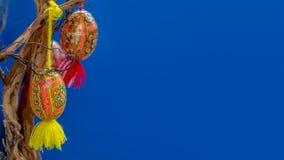 Les oeufs de fond de Pâques peints avec les ornements nationaux ukrainiens accrochent sur des branches Photographie stock