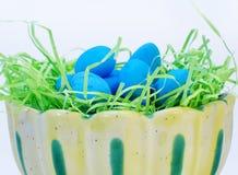 Les oeufs de pâques bleus sur le vert de limette s'emboîtent dans la cuvette jaune Photo libre de droits