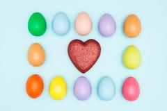 Les oeufs de pâques colorés autour du coeur forment, des valentines Photos stock